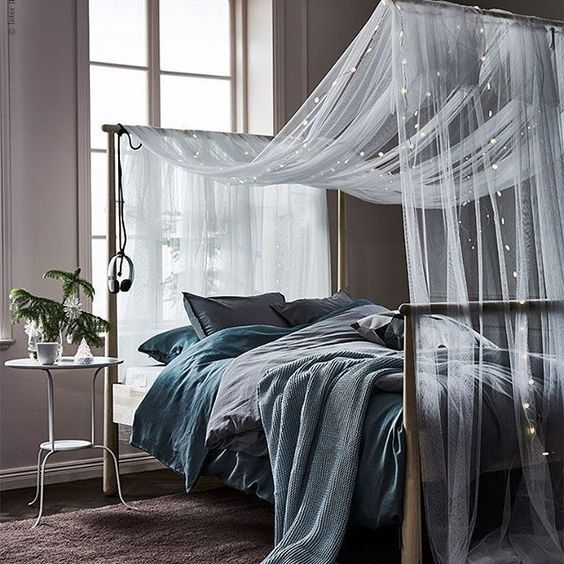a sheer and airy bed canopy with string lights for comfortable sleeping