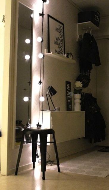 a string of lights accents the narrow wall mirror and adds light to the small space