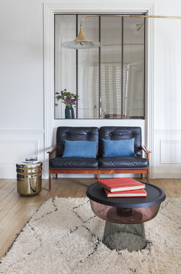 A leather upholstered loveseat and a metallic side table are perfect for the space