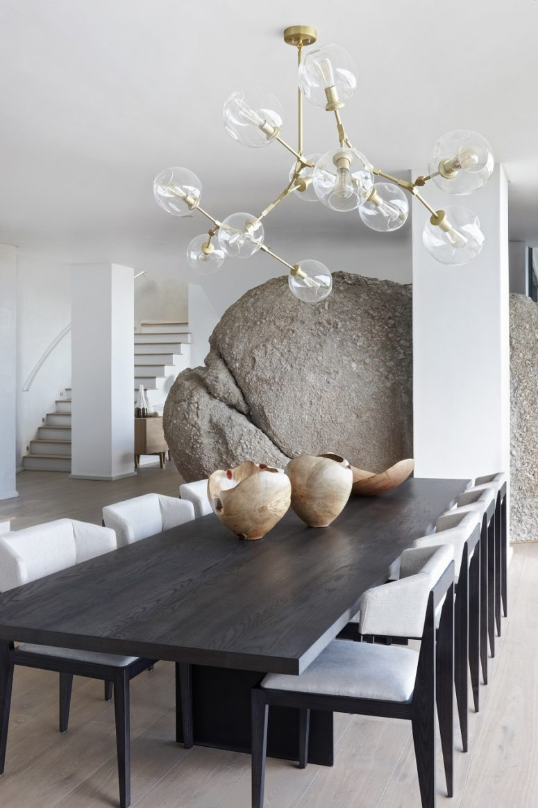 The dining and living spaces are separated with an oversized boulder
