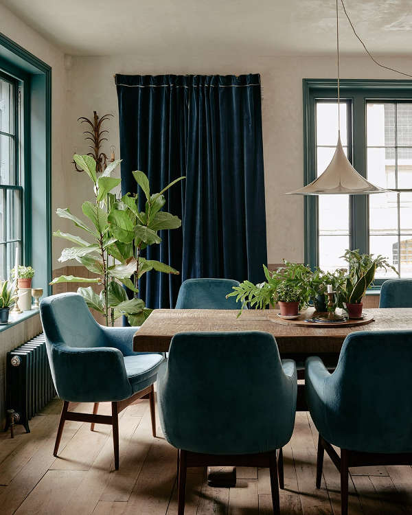 The dining room shows off dark green and blue accents with light-colored and warm-colored wood