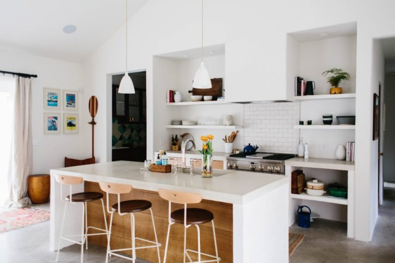 The kitchen is done in white, with a subway tile backsplash, a white kitchen island and countertops