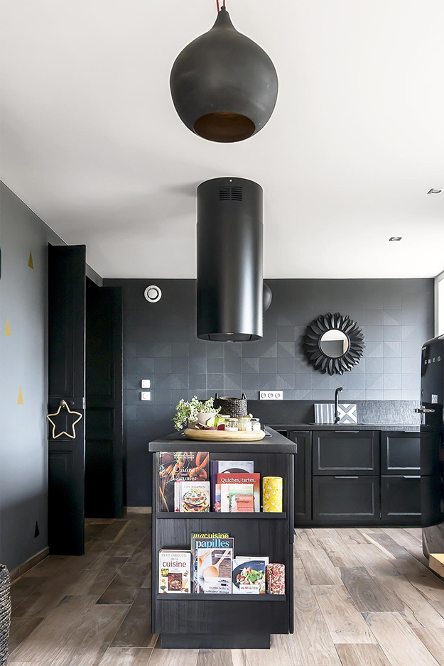 The kitchen is done with a lot of black   black walls, tiles, appliances, cabinets