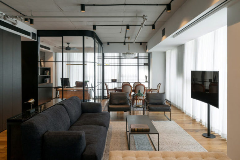 The living room and dining space are united into one but visually separated with a couple of chairs and a side table