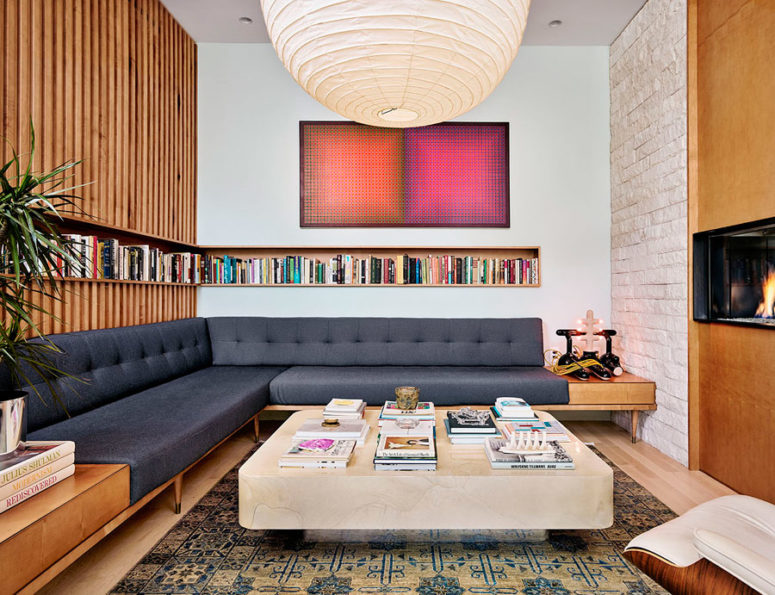The living room is done with a large corner sofa, a built-in bookshelf and is centered around the fireplace