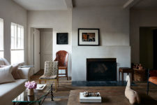 04 The walls are done with white plaster, the floor is of weathered wood, a fireplace adds coziness and baskets too