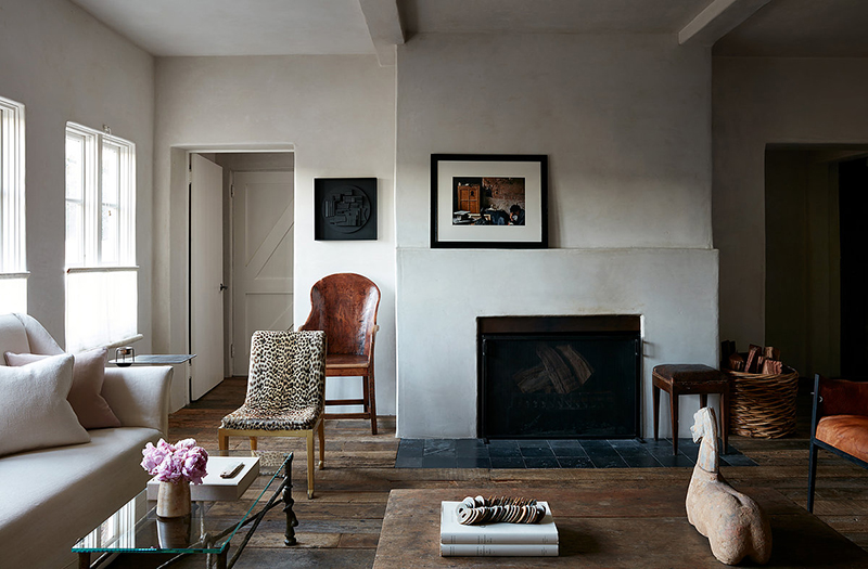 The walls are done with white plaster, the floor is of weathered wood, a fireplace adds coziness and baskets too