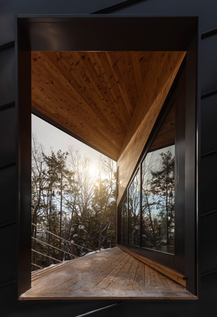 The wooden deck allows to enjoy the views and forests around, and warm-colored timber combines nice with black metal