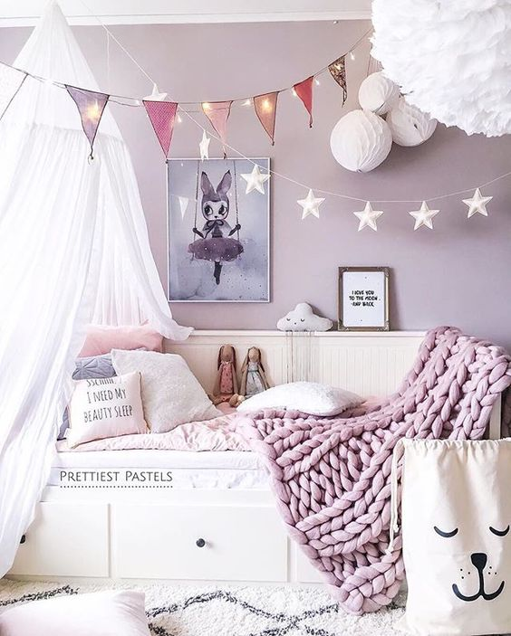 a bunting with string lights over the bed to make the sleeping space cozy