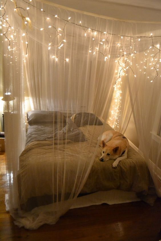 a sheer fabric canopy with string lights to highlight the sleeping space and make it comfier
