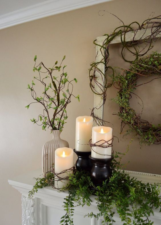 a vine wreath with greenery, pillar candles and cascading greenery plus some in a vase