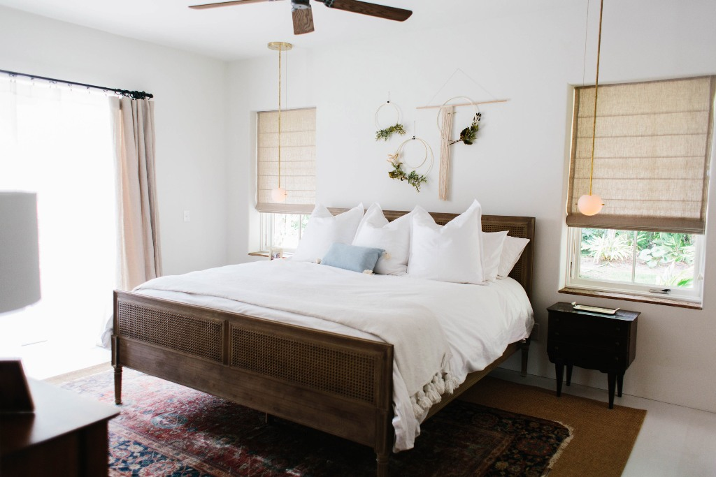 I love the wooden bed and floral hangings over it, vintage rugs and Roman shades bring that tropical and boho feel