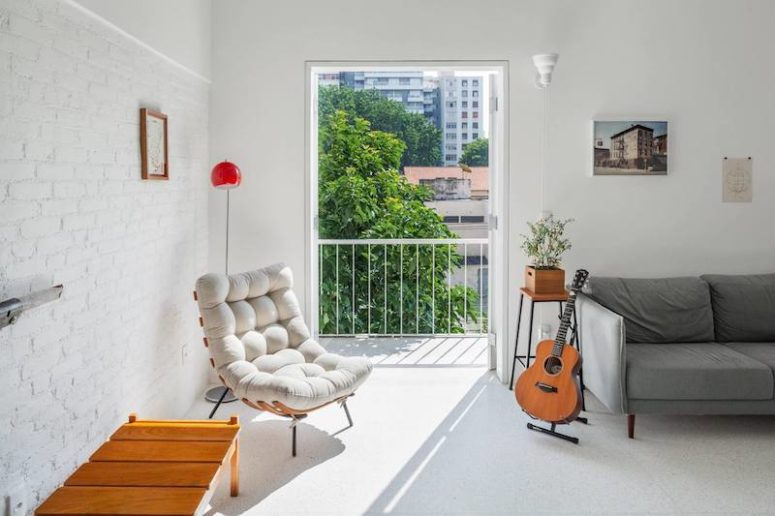 One wall is an exposed brick one, there's a small balcony and a comfy sitting nook next to it