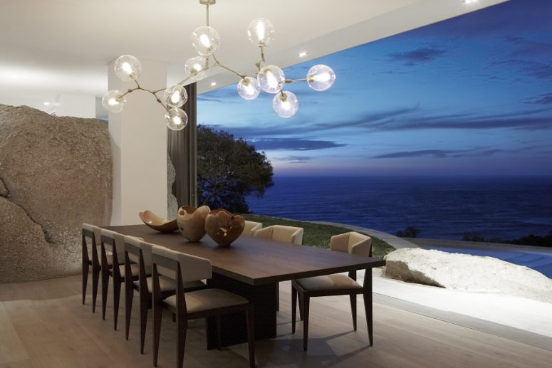 The dining space can be fully opened to outdoors and features a cool bubble chandelier and a chic dining set