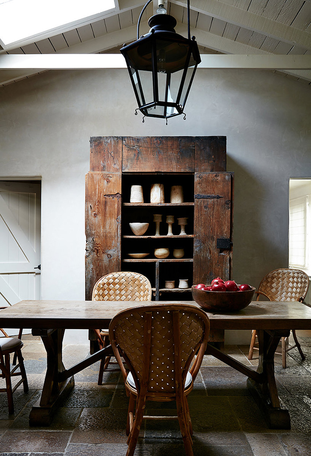 The dining space shows off a fantastic antique weathered cupboard, some woven chairs and a rustic dining table