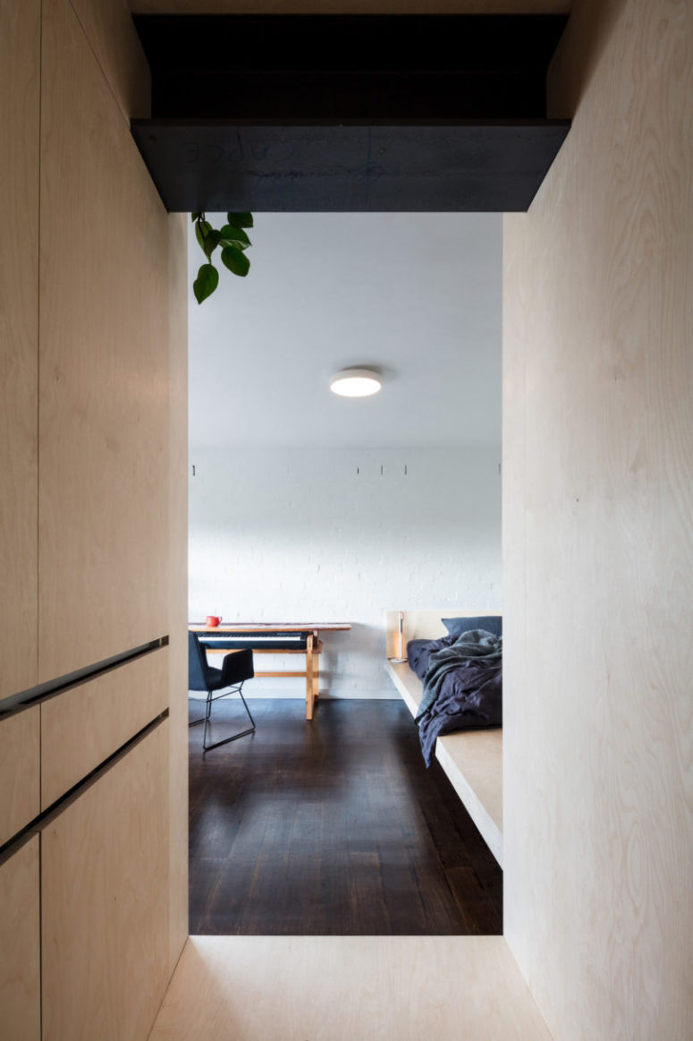 The interest is added to the space with a white brick wall, dark wooden floors that contrast the light-colored plywood