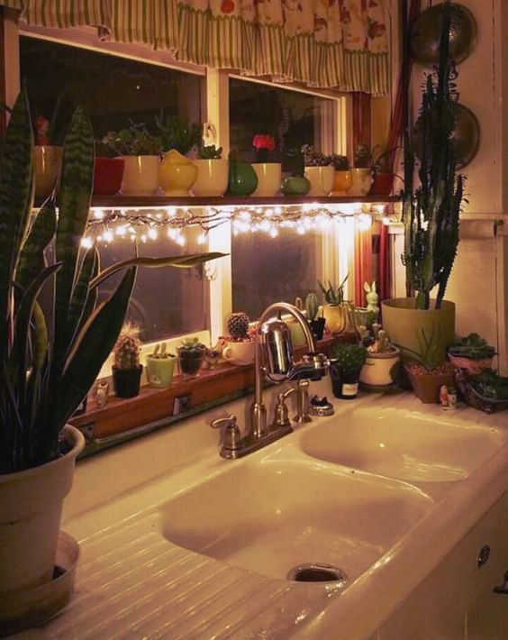 the shelf across the window is lit up with string lights to make the space cozier