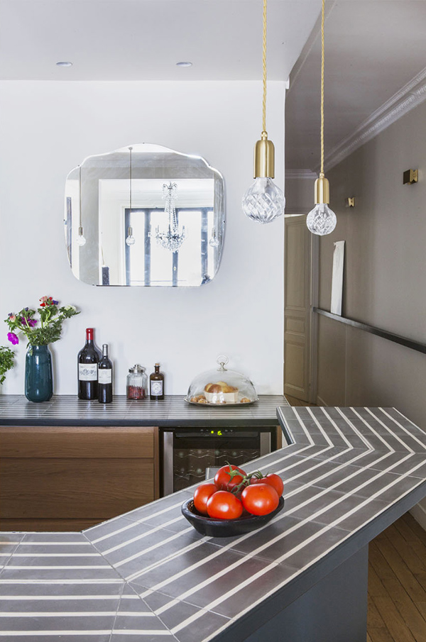 The countertops are striped, and a mirror reflects light and makes the space more glam