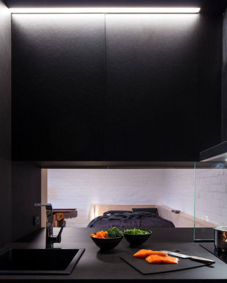 The kitchen is all-black and features a pass through window to the room to make eating and having drinks comfier