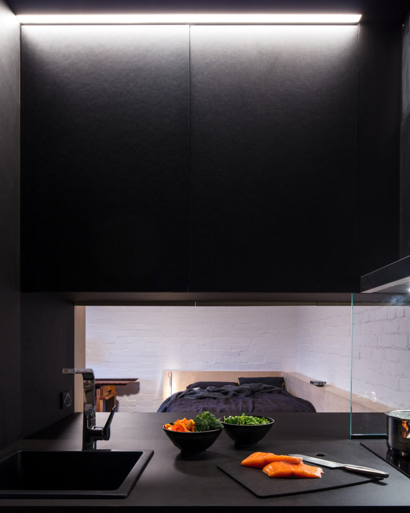 The kitchen is all black and features a pass through window to the room to make eating and having drinks comfier