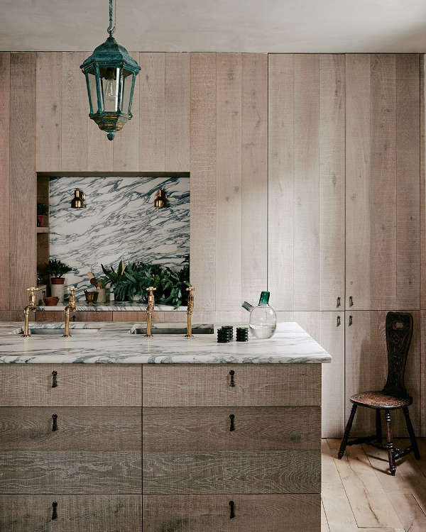 The kitchen is clad with untreated wood, there are elegant marble and brass accents