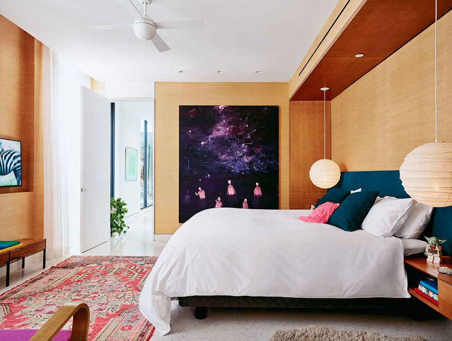 The master bedroom is done with light colored wood, an upholstered wall and a very bold artwork that catches an eye