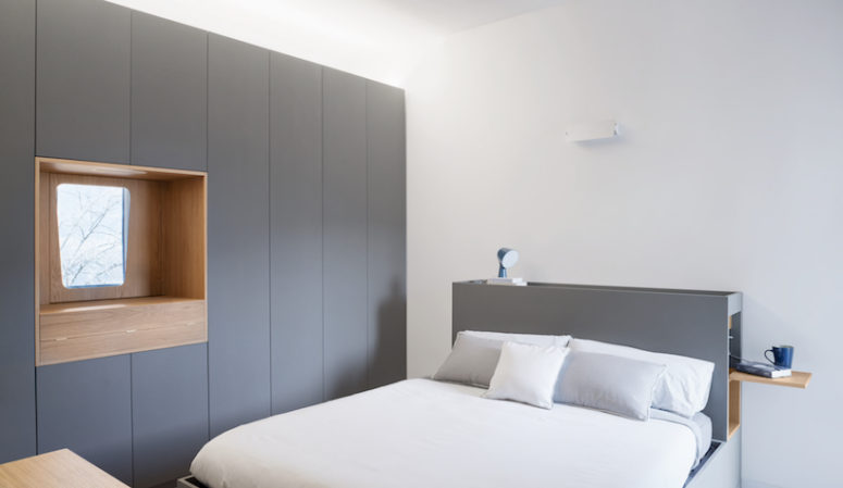 The master bedroom shows off a grey clad wall, a make up space, a grey bed with a storage headboard