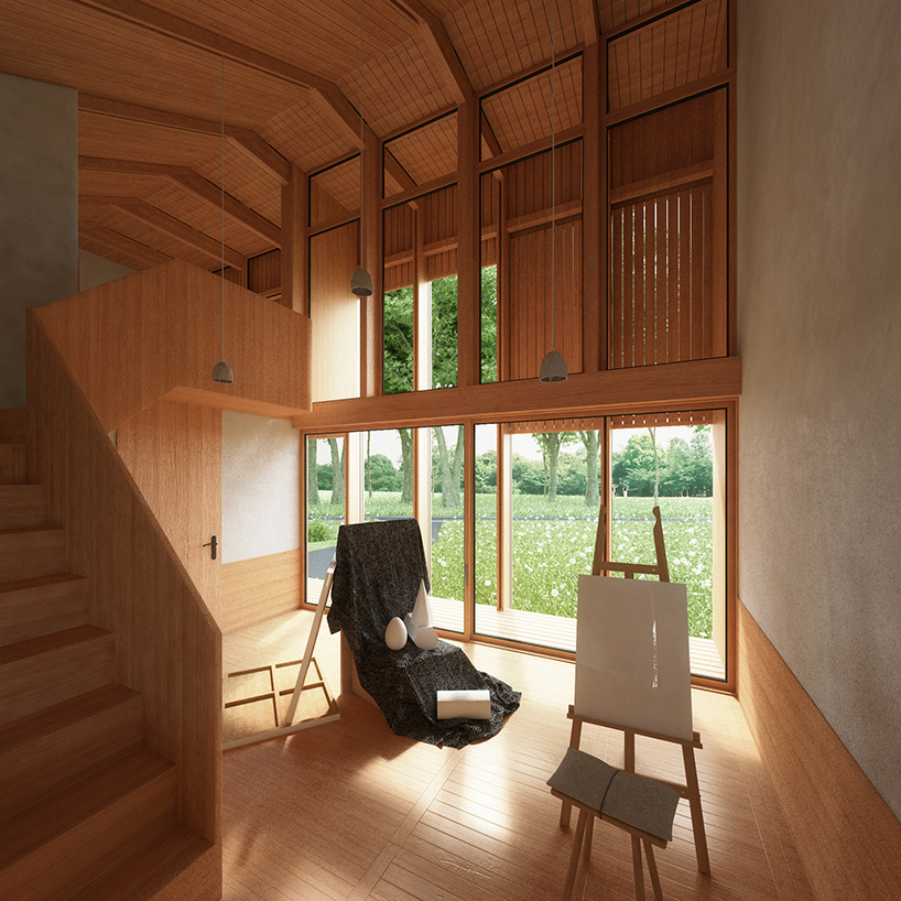 There's much light colored wood, pendant lamps and large windows that overlook the wood or garden