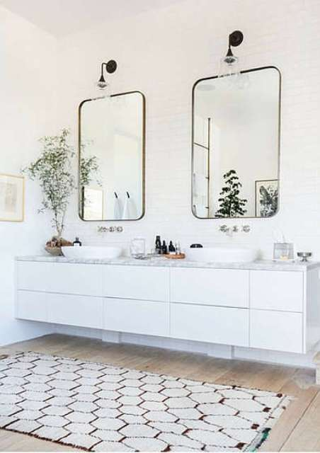 You can also see a floating vanity with a marble top, two mirrors and a cozy rug