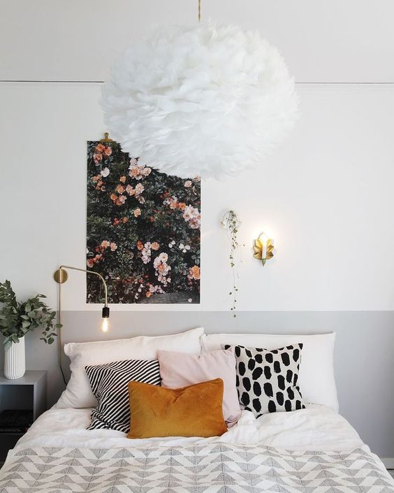 a pretty floral wall art and a fluffy chandelier that reminds of a large bloom