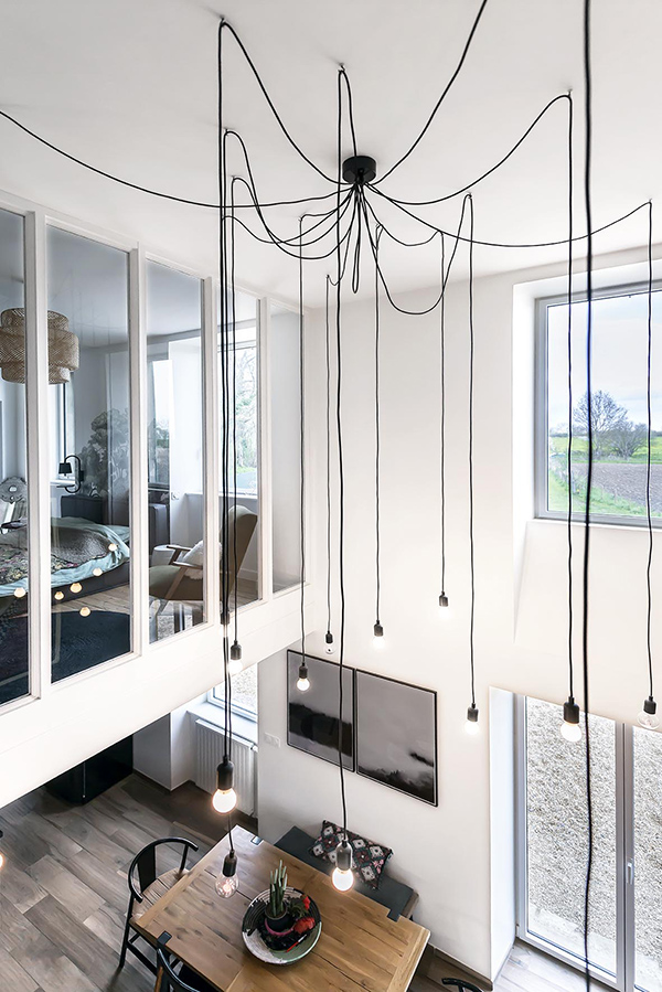 A modern and industrial chandelier highlights the height of the ceiling and brings more light to the bedroom above
