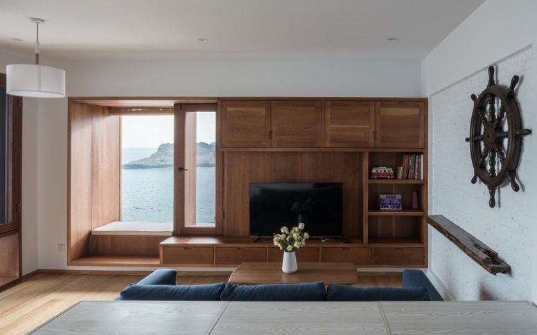 Large windows with comfy windowsills allow enjoying the views of the sea
