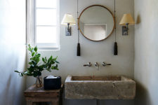 07 The bathroom is done with a stone sink, a wooden stand and bucket and some traditional sconces