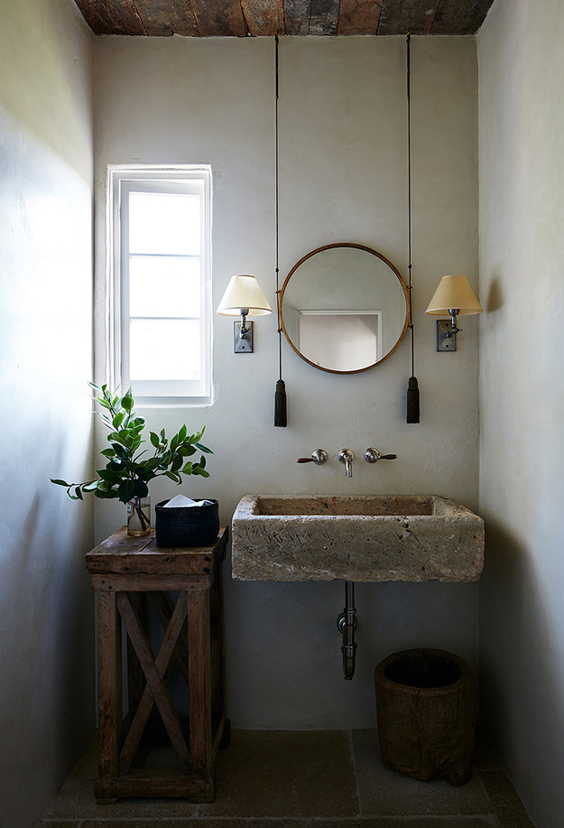 The bathroom is done with a stone sink, a wooden stand and bucket and some traditional sconces
