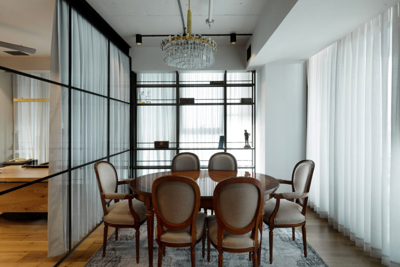 The dining space is done with comfy upholstered chairs, a round table and a glam chandelier