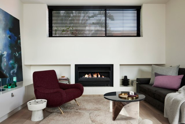 The living space is done with a comfy chair and sofa, a bold table on geometric stone legs and a built-in fireplace