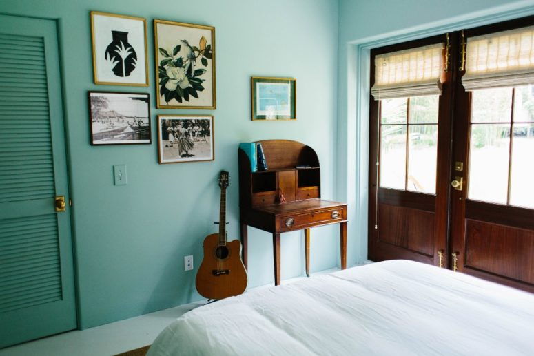 This bedroom is done in turquoise to remind of the ocean, and the artworks are mid-century modern ones