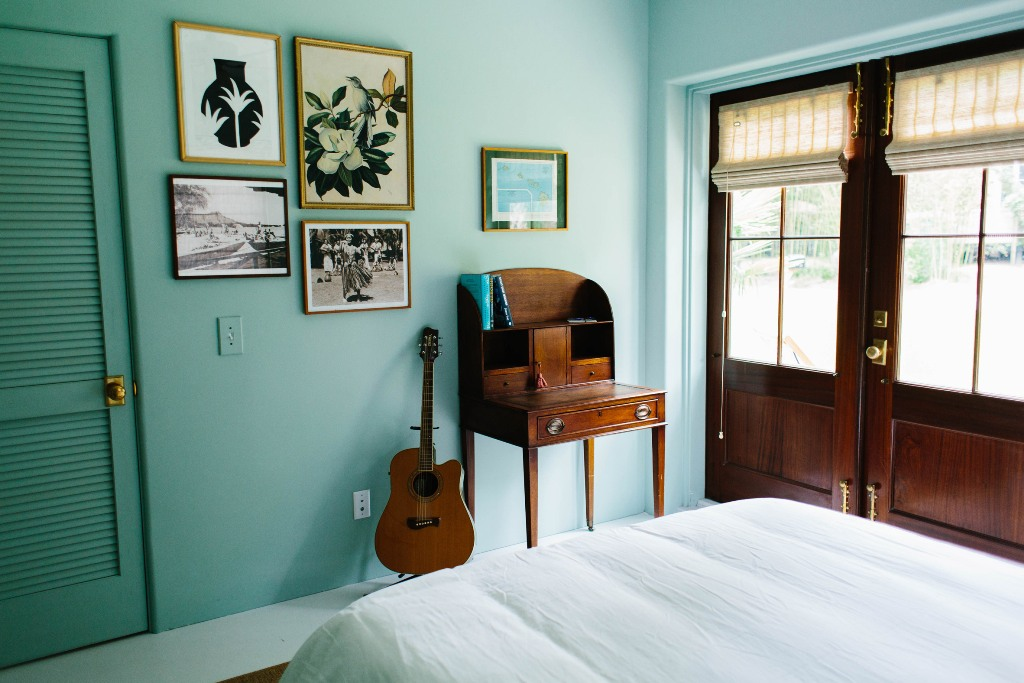 This bedroom is done in turquoise to remind of the ocean, and the artworks are mid century modern ones
