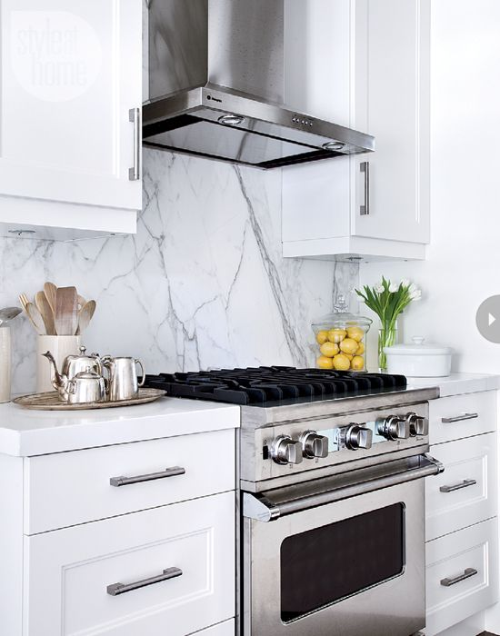 a cool sleek marble backsplash for an eye-catchy touch in a white kitchen