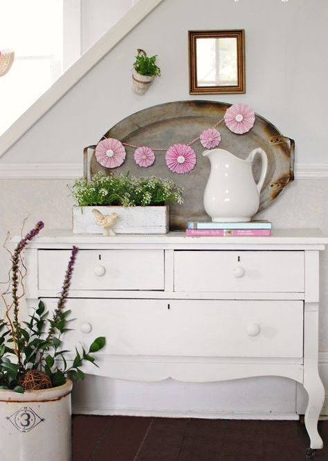 a vintage sideboard console, potted flowers and a cute pink paper fan garland