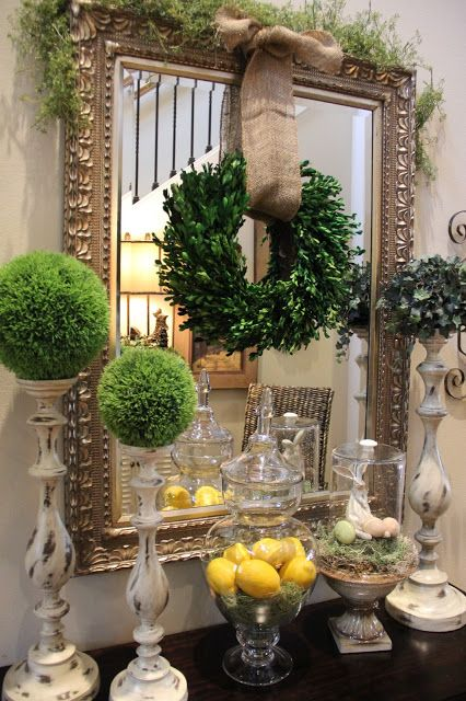 moss topiaries, a boxwood wreath with burlap, a greenery covered mirror and some lemons in a jar