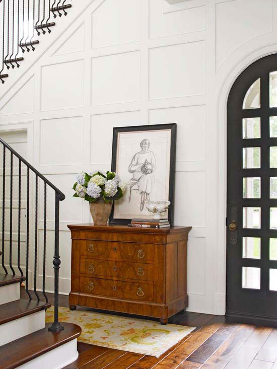 this entryway is spruced up with moldings on the walls and an antique sideboard