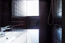 08 The bathroom is clad with black tiles and red grout for a stylish masculine-inspired look
