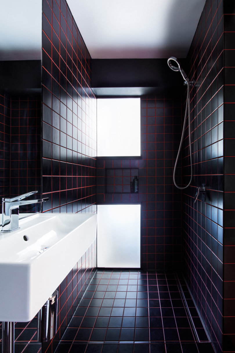 The bathroom is clad with black tiles and red grout for a stylish masculine inspired look