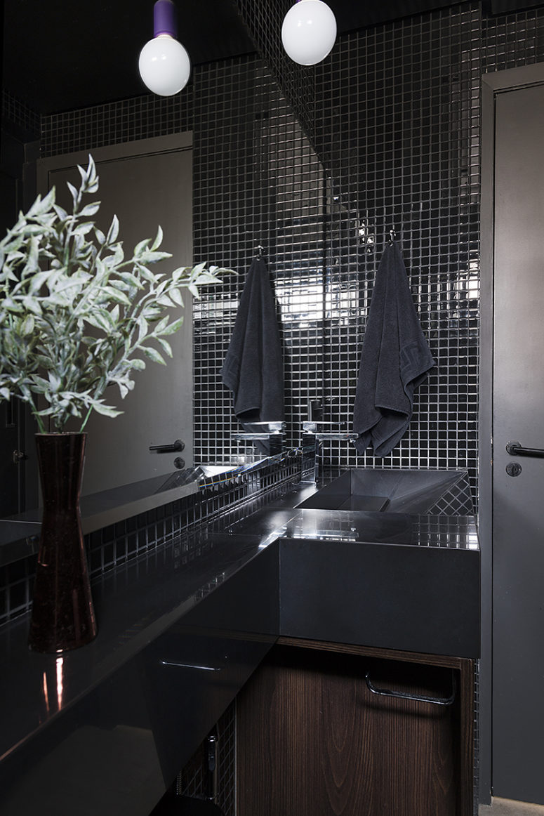 The bathroom is clad with black tiles, white grout and there are black surfaces