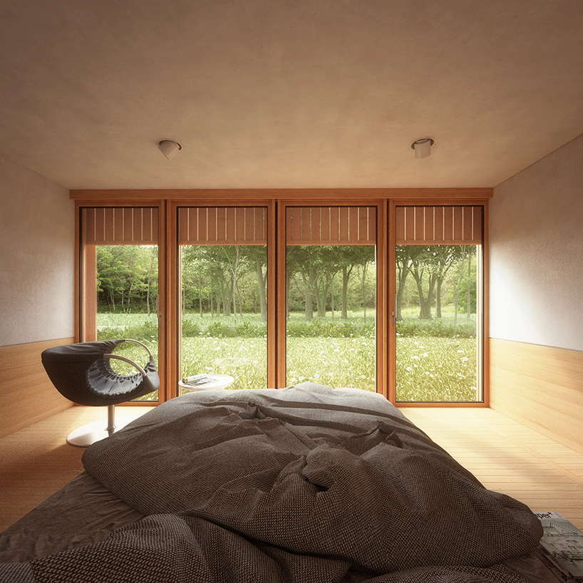 The bedroom features a large bed and a comfy chair, the window overlooks the woodland