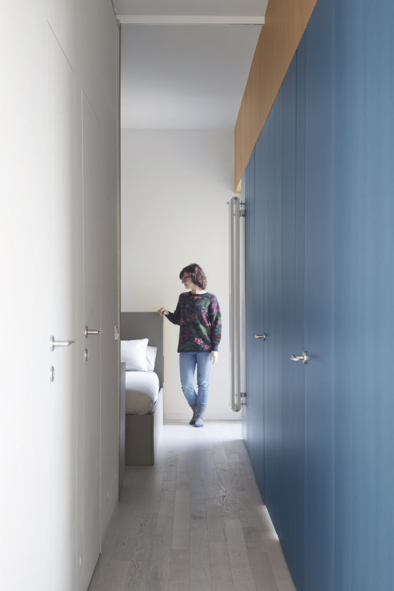 The storage is hidden in the blue and white built-in cabinets in the corridor
