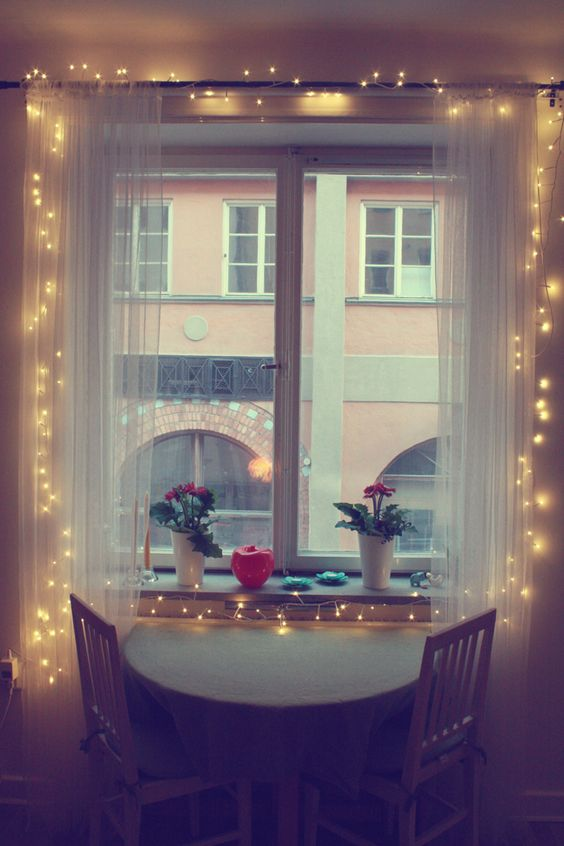 a little breakfast nook becomes inviting with sheer curtains and string lights inside them
