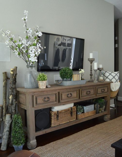 a rustic vintage console table styled with potted greenery and fresh blooms