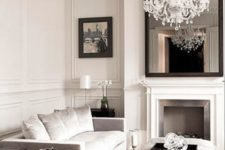 08 molding on the walls and ceiling and a glam crystal chandelier define this living room